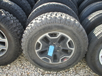 """Image Five Jeep JKU 17"""" Black and milled aluminum Rubicon style wheels with tires"""